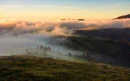 滚动在小山的雾在日出 免版税库存图片