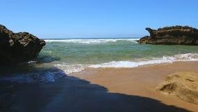 滚动在金黄海岸上的浪潮起伏的海洋泡沫似的波浪在两个岩石之间的微小的海湾 影视素材