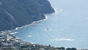 滚动它的水的天蓝色的小波海沿岸航行与山,表面太阳闪烁 股票录像