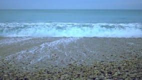 滚动岸上在慢动作, Pebble海滩的泡沫似的海浪在有雾的天空下 股票视频