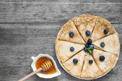 滚动的传统俄国或乌克兰薄煎饼用新鲜的蓝莓、蜂蜜和薄菏早餐 免版税库存照片