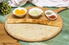 滚动的绉纱、俄国俄式薄煎饼在木切板用开胃菜做用红萝卜和夏南瓜和糖浆 库存照片