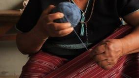 滚动蓝色被洗染的螺纹的球当地卡伦Sgaw小山部落妇女为准备编织传统衣物和cra的手 影视素材