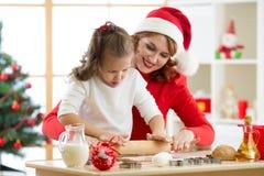 滚动面团的家庭母亲和孩子,在节日装饰的室烘烤圣诞节曲奇饼 库存图片