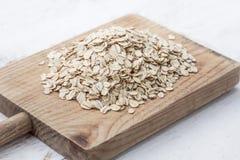 滚的燕麦 格兰诺拉麦片、谷物或者燕麦粥在白色木老ta 免版税库存照片