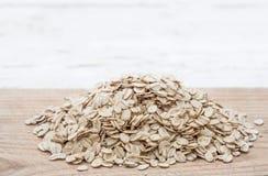 滚的燕麦 格兰诺拉麦片、谷物或者燕麦粥在白色木老ta 免版税图库摄影