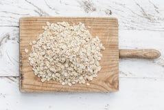 滚的燕麦 格兰诺拉麦片、谷物或者燕麦粥在白色木老ta 库存图片