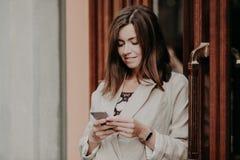 满意的女实业家拿着现代手机,穿戴在白色夹克,查寻互联网,被连接到无线wifi,姿势  免版税库存照片