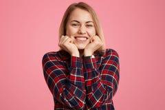 满意的妇女接近的射击在心情握下巴,广泛地微笑,显示白色完善的牙,是,穿戴随便, 免版税库存图片