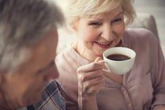 满意的年长妇女饮用的茶 免版税库存图片