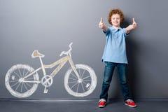 满意的男孩和黄色自行车 免版税库存照片