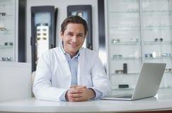 满意的眼科医生与膝上型计算机一起使用 免版税库存图片