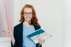 满意的自由职业者在下星期写未来规划,研究为起动做准备,做在笔记薄的笔记,拿着笔,看 免版税库存图片