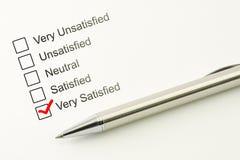 满意的顾客服务反馈 消费者满意程度概念 与一支笔的明显的复选框在纸背景 免版税库存照片