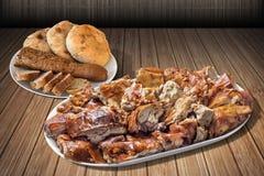 满盘唾液与长方形宝石布朗缺一不可的面包裁减的烤猪肉在竹位置字块和三个皮塔饼面包大面包设置的切片 库存照片