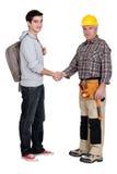 满足新的学徒的有经验的匠人 免版税库存照片