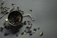 滤茶器用在黑暗的背景,顶视图的疏散绿茶 库存照片