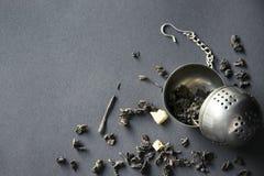 滤茶器用在黑暗的背景,顶视图的疏散绿茶 免版税库存图片