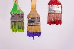 滴下湿油漆红色紫色和绿色油漆的三支画笔 免版税图库摄影