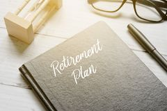 滴漏、镜片、笔和笔记本写与退休计划在与太阳的白色木背景飘动 图库摄影