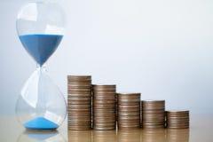 滴漏蓝色沙子和堆硬币 r 免版税图库摄影