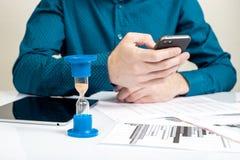 滴漏 工作在办公室的商人在背景中 概念时间是货币 免版税库存照片