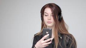 年轻漂亮的女人无线耳机用途片剂和电话拍照片 股票视频