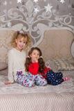 漂亮的孩子充当他们的在床上的睡衣在goin前 免版税库存图片