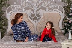 漂亮的孩子充当他们的在床上的睡衣在goin前 库存照片