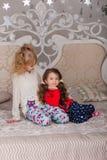 漂亮的孩子充当他们的在床上的睡衣在goin前 免版税库存照片