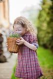 漂亮的孩子女孩在春天庭院里嗅到会开蓝色钟形花的草花篮子  库存图片