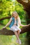 漂亮的孩子女孩坐日志在河下户外 免版税库存图片