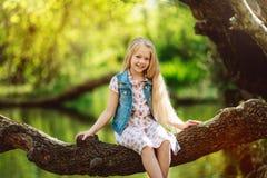 漂亮的孩子女孩坐日志在河下户外 库存图片