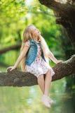 漂亮的孩子女孩坐日志在河下 免版税库存图片