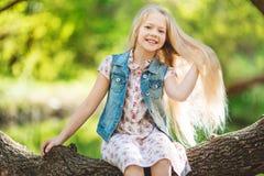 漂亮的孩子女孩坐日志在河下 免版税图库摄影