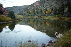 漂泊小船停泊了在一条平静的河的边缘 库存照片