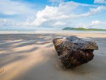 漂流木头注册与看法蓝天和白色云彩的一个海滩 库存照片