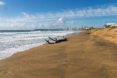 漂流木头注册空的海滩和蓝色多云天空 免版税库存照片
