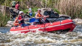 漂流,划皮船 一群人橡胶可膨胀的小船的在水一条风雨如磐的小河  免版税库存图片