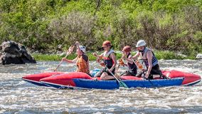 漂流,划皮船 一群人橡胶可膨胀的小船的在水一条风雨如磐的小河  库存照片