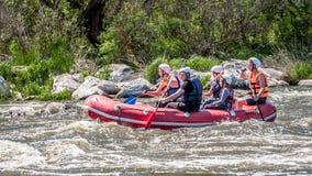 漂流,划皮船 一群人橡胶可膨胀的小船的在水一条风雨如磐的小河  图库摄影