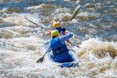 漂流,划皮船 两位运动员在一条开水小河的橡胶可膨胀的小船航行 配合 免版税库存照片