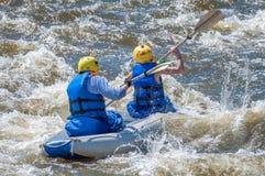 漂流,划皮船 两位运动员在一条开水小河的橡胶可膨胀的小船航行 配合 库存图片