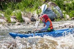 漂流,划皮船 在橡胶可膨胀的小船的女孩航行在水一条风雨如磐的小河  水飞溅特写镜头 库存图片