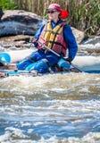 漂流,划皮船 在橡胶可膨胀的小船的女孩航行在水一条风雨如磐的小河  水飞溅特写镜头 免版税库存图片