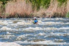漂流,划皮船 桨特写镜头视图有飞溅的水 一艘小皮船的一个人在水一条风雨如磐的小河  免版税库存照片