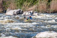 漂流,划皮船 桨特写镜头视图有飞溅的水 一艘小皮船的一个人在水一条风雨如磐的小河  库存图片