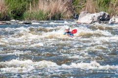 漂流,划皮船 桨特写镜头视图有飞溅的水 一艘小皮船的一个人在水一条风雨如磐的小河  免版税库存图片