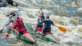 漂流,划皮船 运动员在一条开水小河的橡胶可膨胀的小船航行 水飞溅特写镜头 免版税库存照片