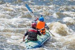 漂流,划皮船 运动器材的两位运动员在一条开水小河的橡胶可膨胀的小船航行 图库摄影